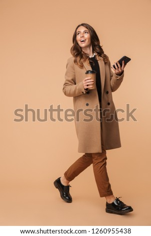 Photo of attractive woman 20s holding takeaway coffee and using  Stock photo © deandrobot