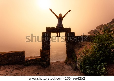 Female sitting on ancient sandstone doorway with foggy sunrise Stock photo © lovleah