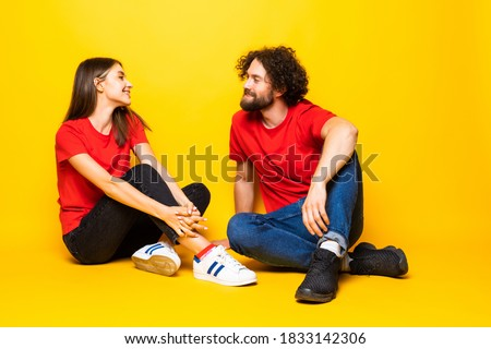 Photo of cute couple man and woman sitting on floor over white w Stock photo © deandrobot