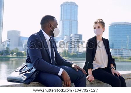 Three intercultural businesswomen in formalwear sitting by table Stock photo © pressmaster