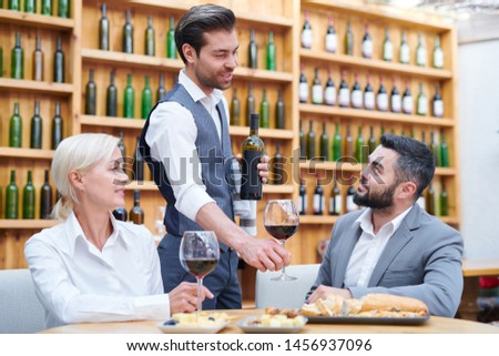 Young elegant waiter or bartender recommending his clients new sort of wine Stock photo © pressmaster