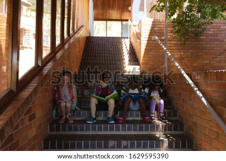 Front view schoolkids reading book while sitting on stairs of elementary school together  Stock photo © wavebreak_media