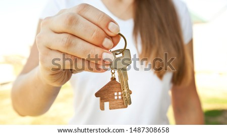 Man's hand gives a key female on background of wooden door. Deal with the real estate concept Stock photo © galitskaya
