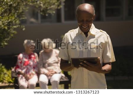 Front view of happy senior man suing digital tablet with senior women on the background in garden Stock photo © wavebreak_media