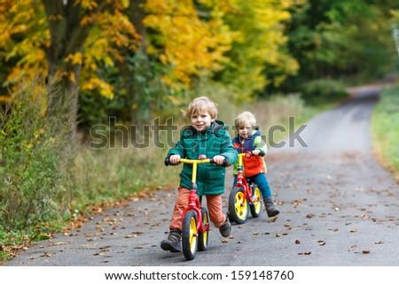 little boy having fun on bikes in autumn forest. Selective focus on boy Stock photo © galitskaya