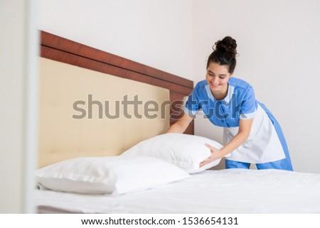 jovem · hotel · empregada · para · cima · travesseiro · cama - foto stock © pressmaster