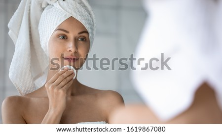 Pretty young healthy woman using cotton pad for applying hydrating cream on face Stock photo © pressmaster