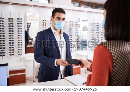 Hands of young female taking pair of new eyeglasses from those of clinician Stock photo © pressmaster
