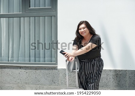 Pretty young Asian businesswoman with suitcase standing in hotel lounge Stock photo © pressmaster