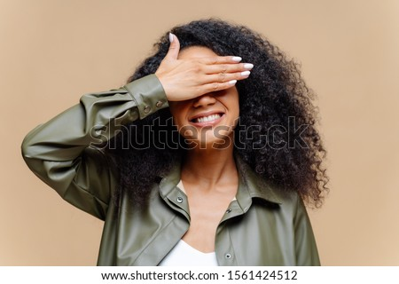 Shy cheerful young Afro woman covers eyes with palm, has toothy smile, hides face, has curly hairsty Stock photo © vkstudio
