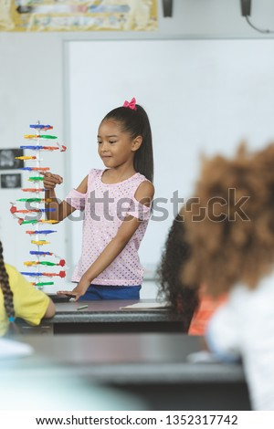 Front view of a mixed-race ethnicity schoolgirl analyzing DNA structure model in classroom at school Stock photo © wavebreak_media