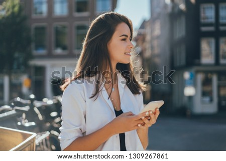 Smiling girl scrolling in smartphone of her friend while both having cappuccino Stock photo © pressmaster