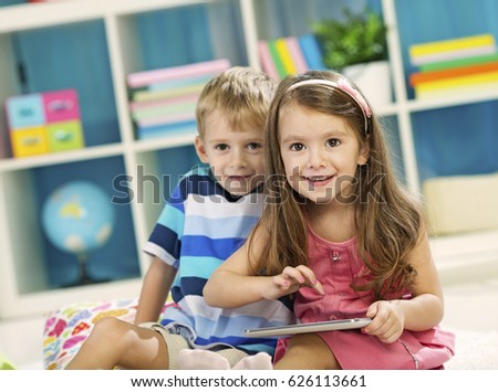 Cheerful little girl with toothy smile holding digital tablet by chest Stock photo © pressmaster