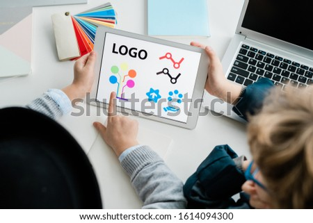 One of two youthful pupils pointing at logo elements on touchpad screen Stock photo © pressmaster