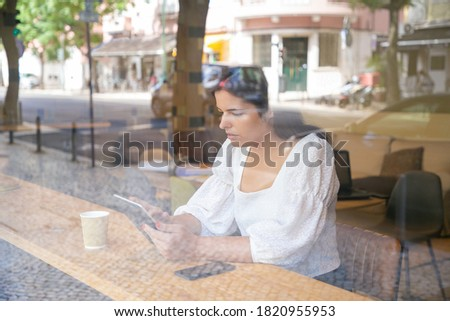 Young pensive businesswoman with glass of coffee and paper moving in elevator Stock photo © pressmaster