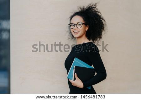 Sideways shot of beautiful dark skinned curly college student dr Stock photo © vkstudio