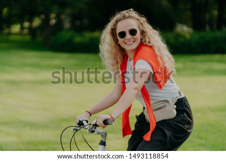Photo of curly European woman keeps hands on handlebar of bicycle, travels outdoor in park, wears sh Stock photo © vkstudio