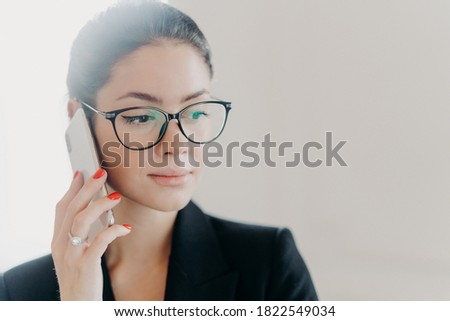 Serious brunette businesswoman with makeup, manicure, wears red jacket, carries diary and notepad, s Stock photo © vkstudio