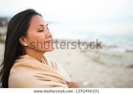 Portrait of beautiful mixed-race woman standing at beach on a sunny day. She is smiling and looking  Stock photo © wavebreak_media