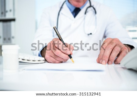 Front view of a Caucasian male doctor writing prescription on notebook to senior woman in clinic roo Stock photo © wavebreak_media
