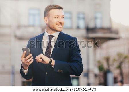 Outdoor shot of prosperous successful unshaven businessman wears Stock photo © vkstudio