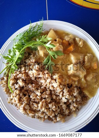 Traditional boiled buckwheat with meat goulash and fresh herbs Stock photo © ElenaBatkova