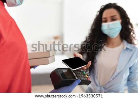 woman wearing surgical mask and Digital contactless thermometer. Stock photo © Margolana