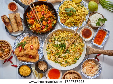 Asian food served. Plates, pans and bowls full of noodles chicken stir fry and vegetables Stock photo © dash