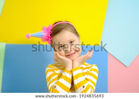 Little blonde girl in pink birthday cap smiling, close her eyes, make a wish Stock photo © Illia