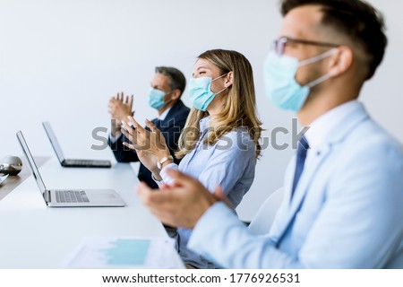 Business people with protcetion masks clapping hands after succe Stock photo © boggy
