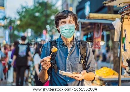 Young man tourist in medical mask eating Typical Korean street food on a walking street of Seoul. Sp Stock photo © galitskaya