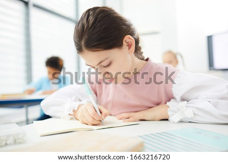 Portrait of a young girl in school at the desk.Horizontal Shot.  stock photo © HASLOO