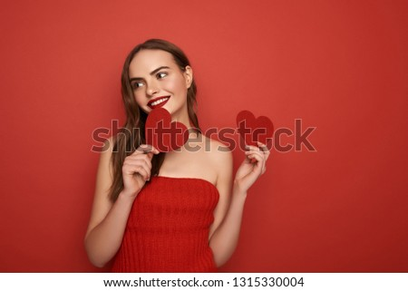 Glamorous woman touching her red dress while looking at camera Stock photo © wavebreak_media