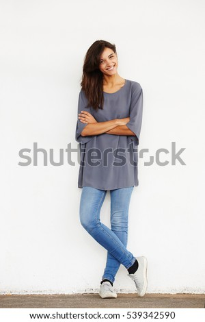Full length portrait of attractive young woman leaning on the wall Stock photo © deandrobot