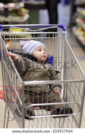 Small girl sit in shoppingcart in supermarket and look to right Stock photo © Paha_L