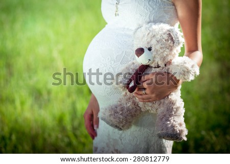 Toy bear cub against a stomach of the pregnant woman. The pregnant woman with a toy bear cub are wal Stock photo © traza