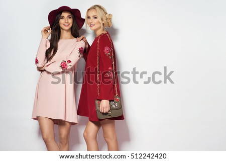 two beautiful fashion models posing outside with shopping bags stock photo © deandrobot