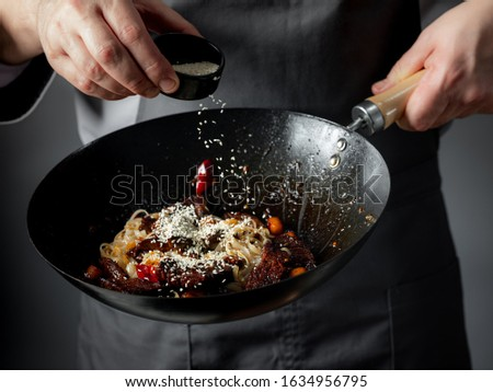 Chinese cook prepares spicy dish fried beef and vegetables. Hands chefs prepare Chinese food close-u Stock photo © mcherevan