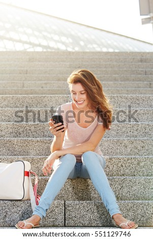 Portrait of happy friends using mobile phones on steps at nightclub Stock photo © wavebreak_media