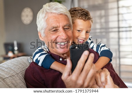 Happy boy with grandfather using smart phone while sitting by wall Stock photo © wavebreak_media