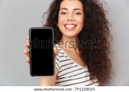 Attractive adult girl with ring in nose demonstrating her mobile Stock photo © deandrobot
