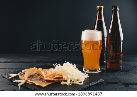 Glass of lager beer with snack on vintage wooden board on black background. Pistachios and pretzel w Stock photo © DenisMArt