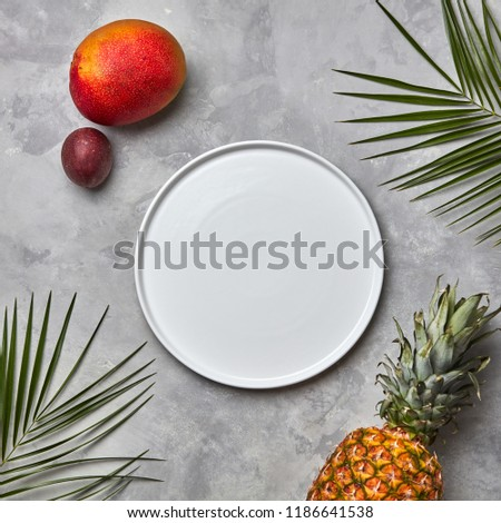 palm leaves empty white plate and a set of different tropical fruits mango passion fruitbanana c stock photo © artjazz