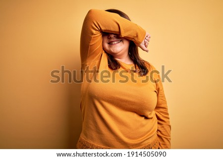 Emotional plus size model standing in studio closing mouth with hand showing surprise astonishment o Stock photo © Traimak