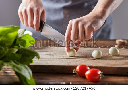 Boiled quail eggs cut female hands on a wooden board on a table with tomatoes and spinach. Step by s Stock photo © artjazz