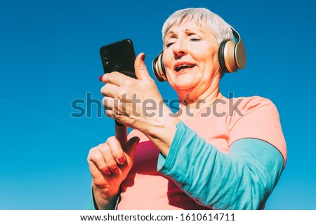 Cheerful sports woman in earphones holding smartphone and looking away Stock photo © deandrobot