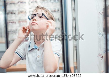 Young boy being very happy with his new eyeglasses in the store Stock photo © Kzenon