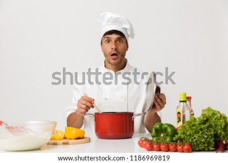 shocked young chef man isolated over white wall background using laptop computer stock photo © deandrobot