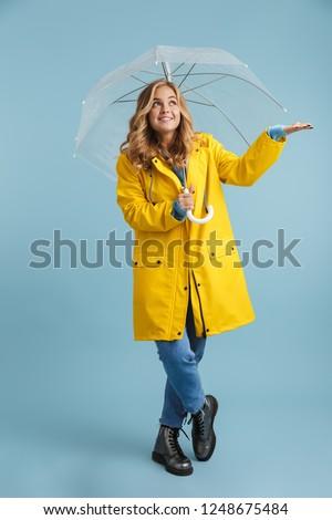 Photo of young woman 20s wearing yellow raincoat looking upward, Stock photo © deandrobot