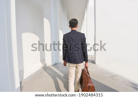 portrait of young businessman with sunglasses holding back of he stock photo © feedough